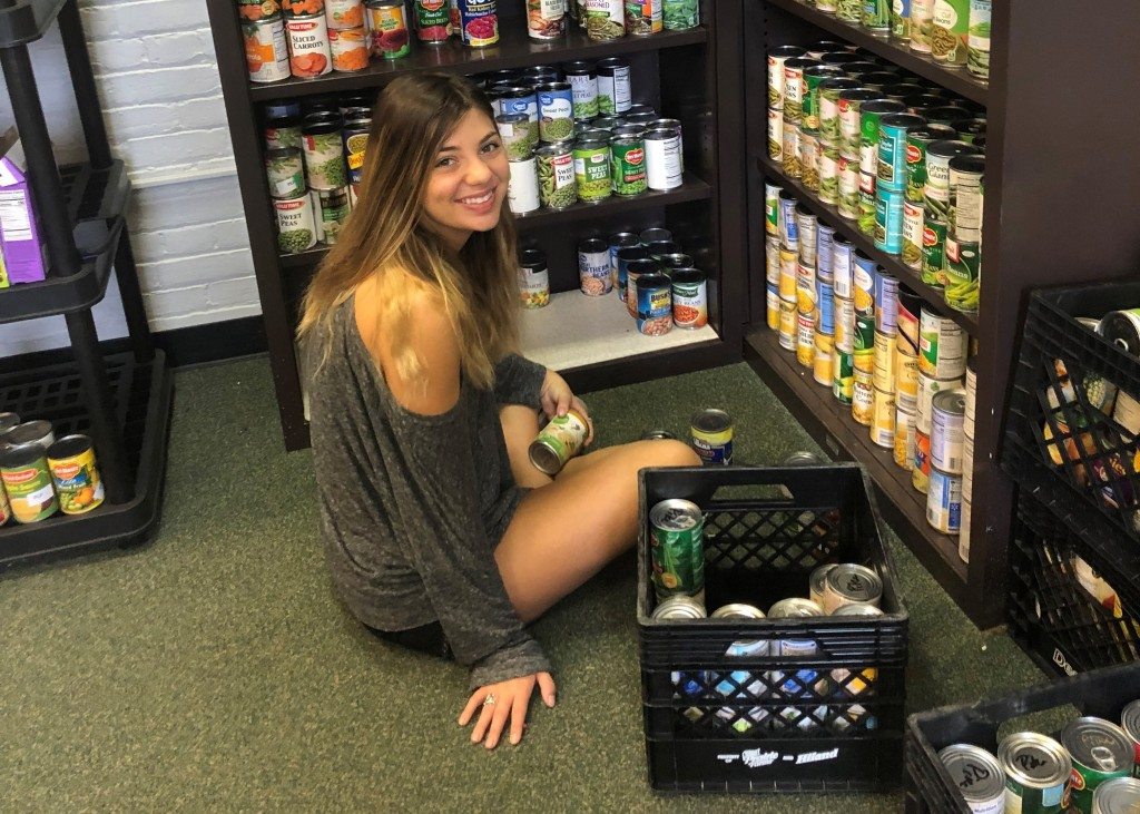 A smiling young woman places cans on a shelf while sitting on the floor.