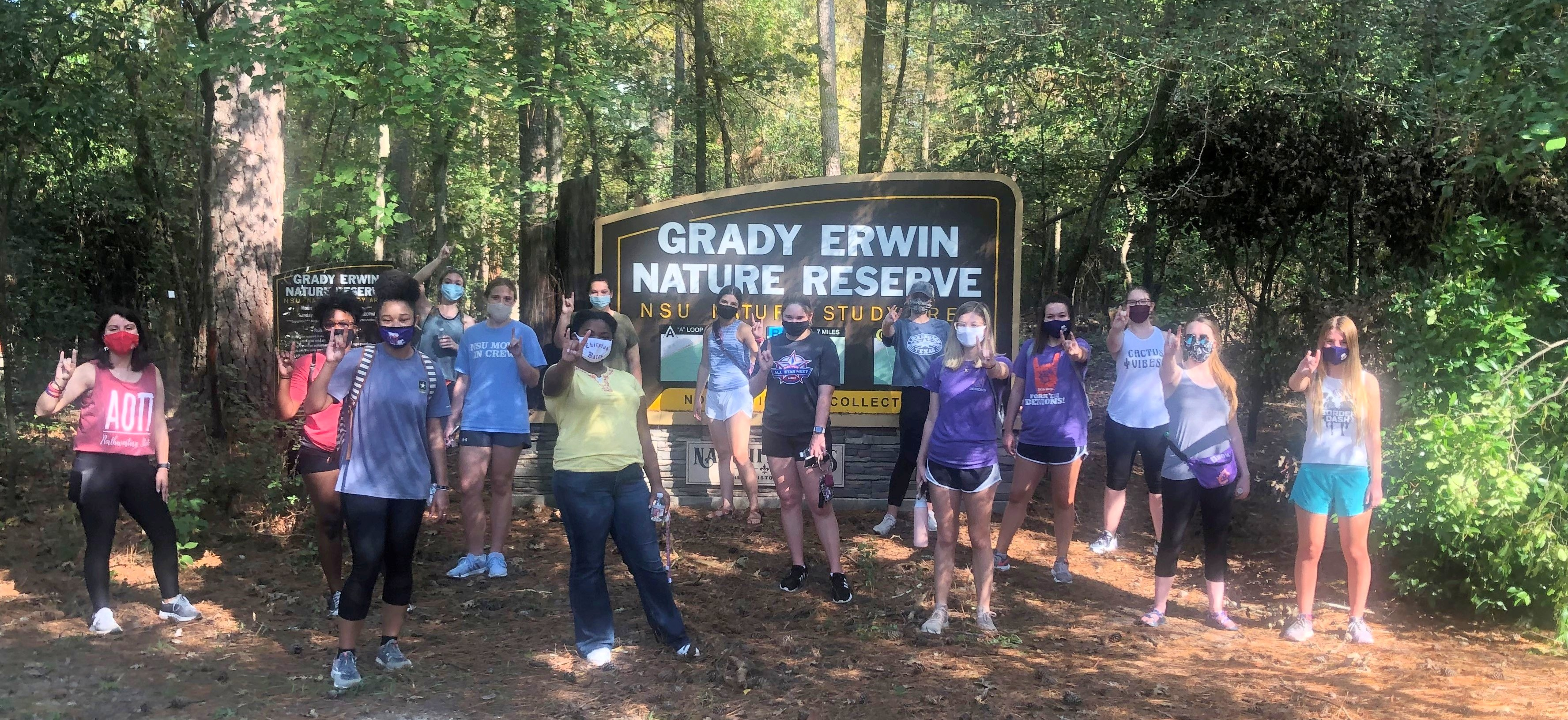 Forest scene. Fifteen masked students pose in front of the Grady Nature Preserve entrance sign.