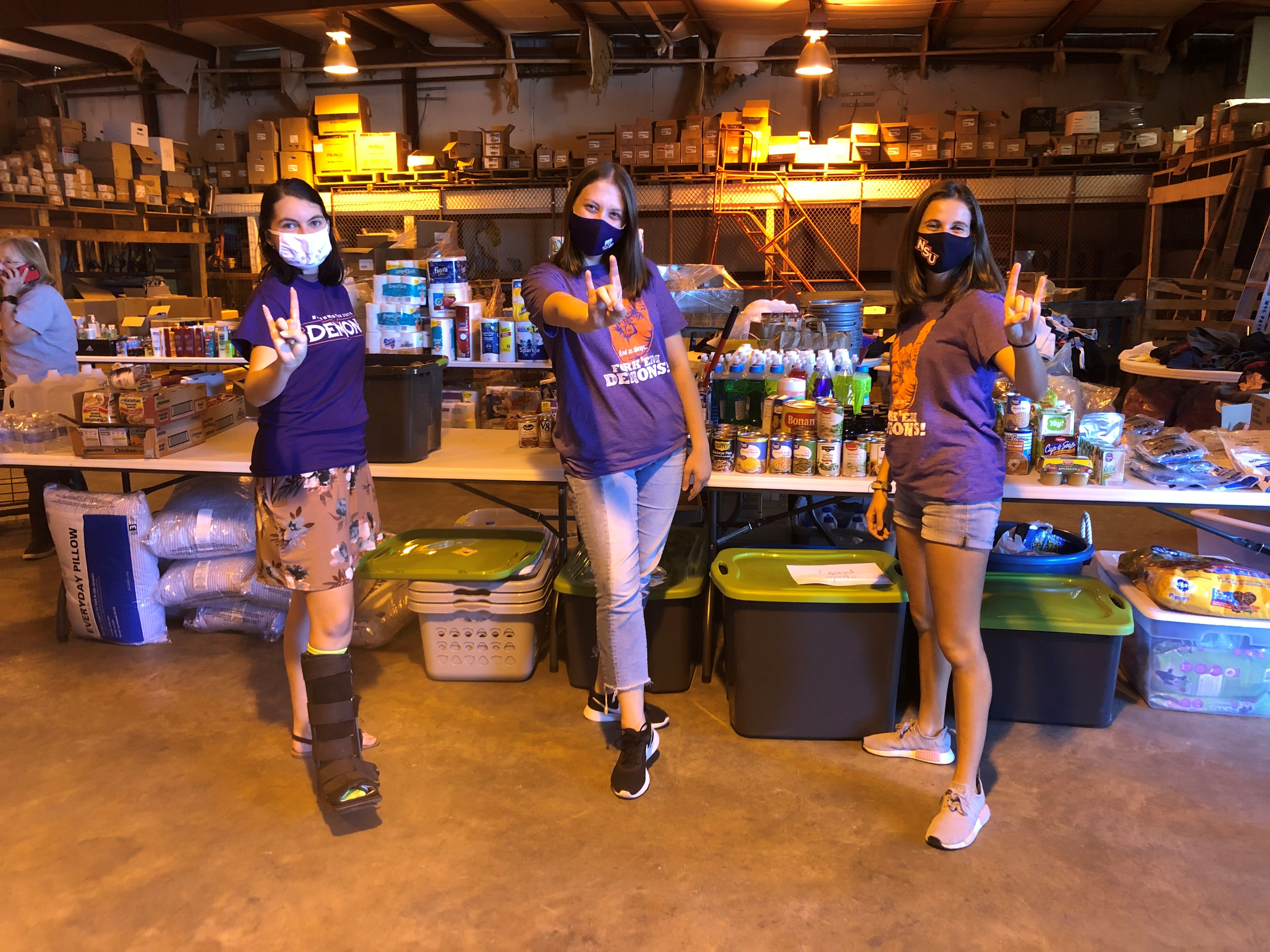 Three students pose in a warehouse in front of tables stacked with food, toiletries, and other hurricane supplies.