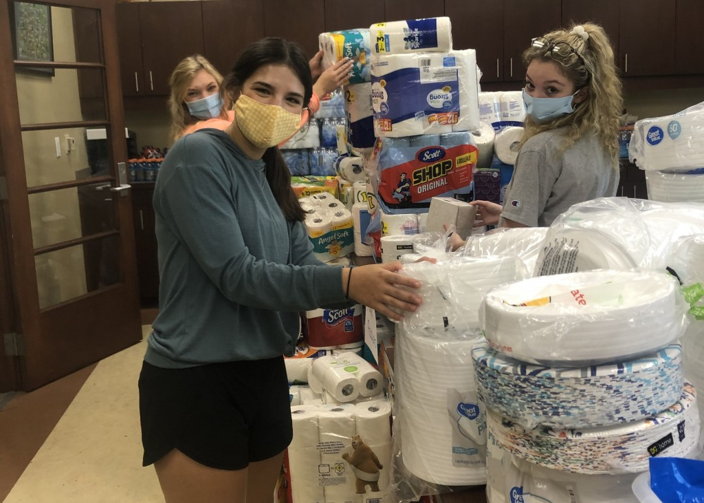 Three mask-wearing students arrange paper towels, toilet paper, and disposable plates.